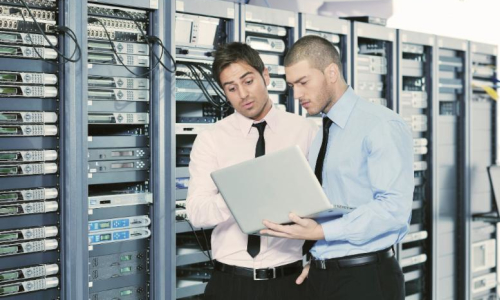 Two engineers working on a laptop in a server room